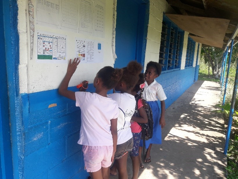 School children reviewing the Vanuatu Climate Update (VCU) placed on community and school notice boards.